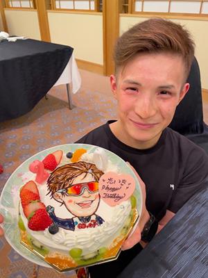 [写真]誕生日ケーキを片手に笑顔を見せる川除選手