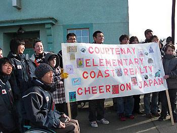 [写真]横断幕を持つ子供達と日本チーム