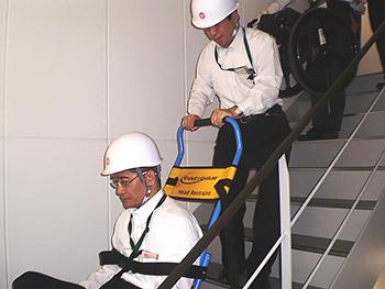 [写真]避難訓練 車いすを操作してもらい階段を降りる