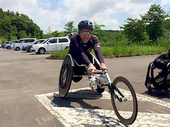 [写真]車いすレーサーに乗る長田弘幸
