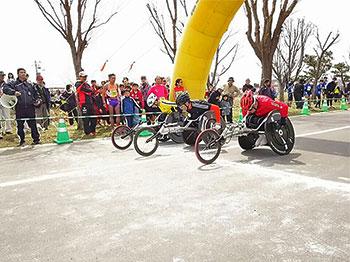[写真]スタートラインに並ぶ車いすの部出場選手