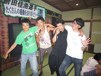 [写真]みんなと肩を組んで歌っている様子