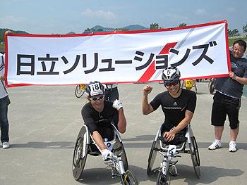 [写真]日立ソリューションズの横断幕の前で長田弘幸選手と久保恒造選手のガッツポーズ