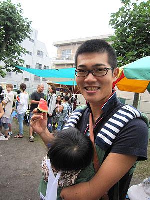 [写真]赤ちゃんを抱っこしている坊主頭の新田選手
