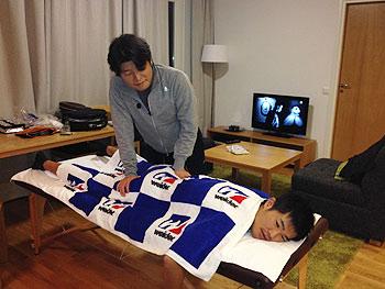 [写真]白戸篤志さんにトレーニング後のケアをしてもらう新田佳浩