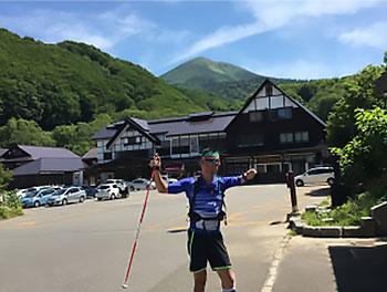[写真]八甲田山を背景に両腕を上げて立つ新田佳浩