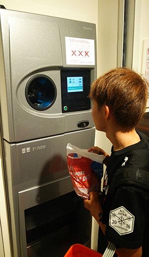 [写真]リサイクルボックスへ瓶を入れる川除選手