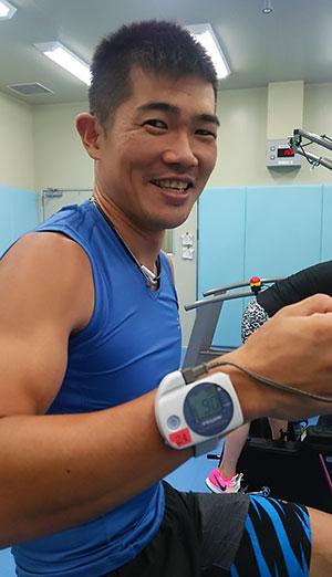 [写真]測定中の新田佳浩選手と手首に装着した測定器