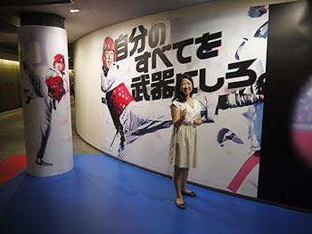 [写真]都営大江戸線パラリンピック競技展示のパラテコンドーのポスターの前でポーズをとる太田渉子