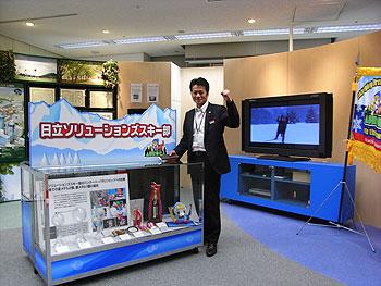[写真]ショールームにてトロフィーやメダルなどの展示の前でガッツポーズする荒井秀樹監督