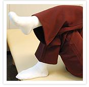 [写真]片方の膝頭の上に、反対側のふくらはぎを乗せる