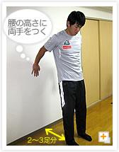 [写真]壁を背にして立つ